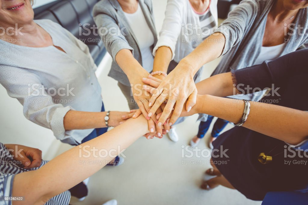 Women's team. Group of women joining hands Women's team. Group of woman joining hands. Close up of hands, high angle view. Adult Stock Photo