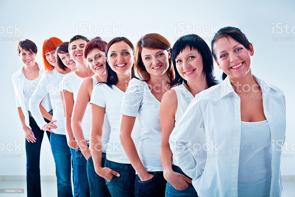 Women's team Group of women standing in the row, smiling at the camera against white background. Adult Stock Photo