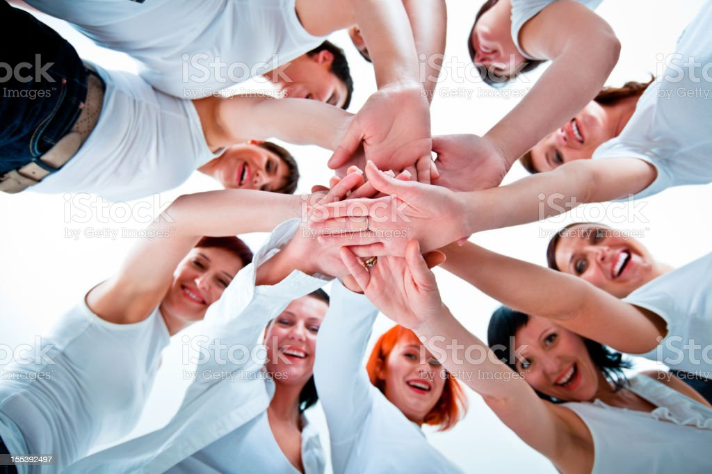 Women's team Teamwork concept. Group of women joining hands. Low angle view, white background. Adult Stock Photo
