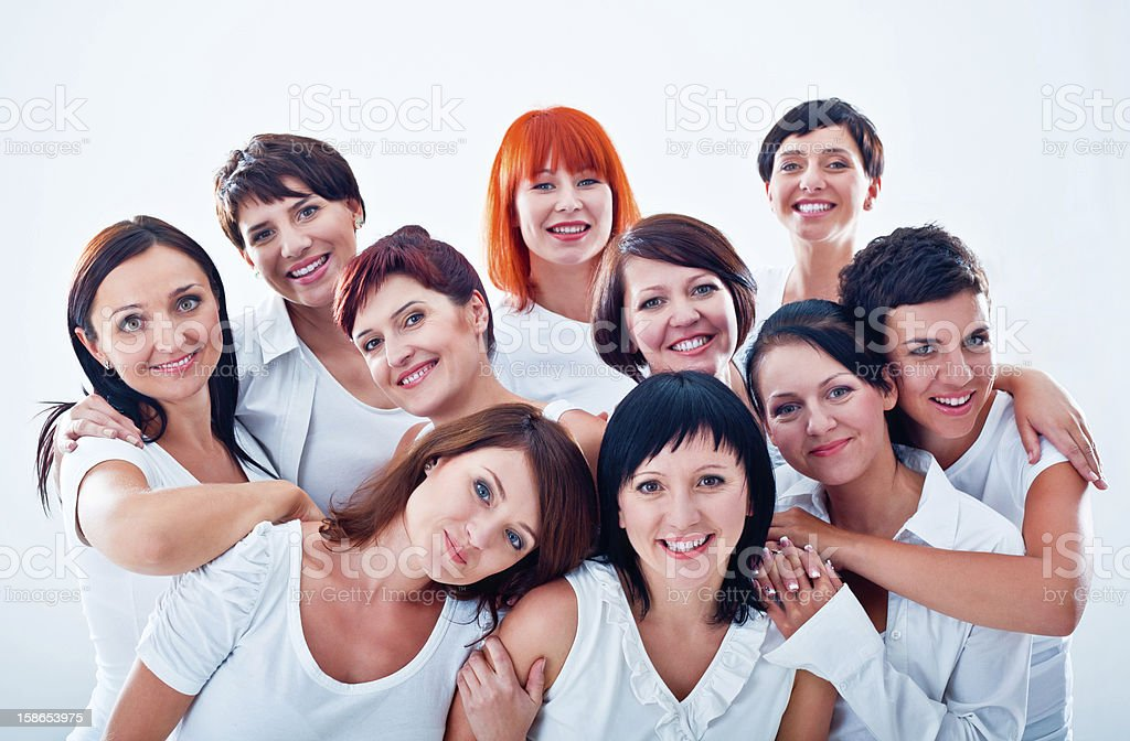 Women's team Large group of happy women standing together against white background, smiling at the camera. Adult Stock Photo