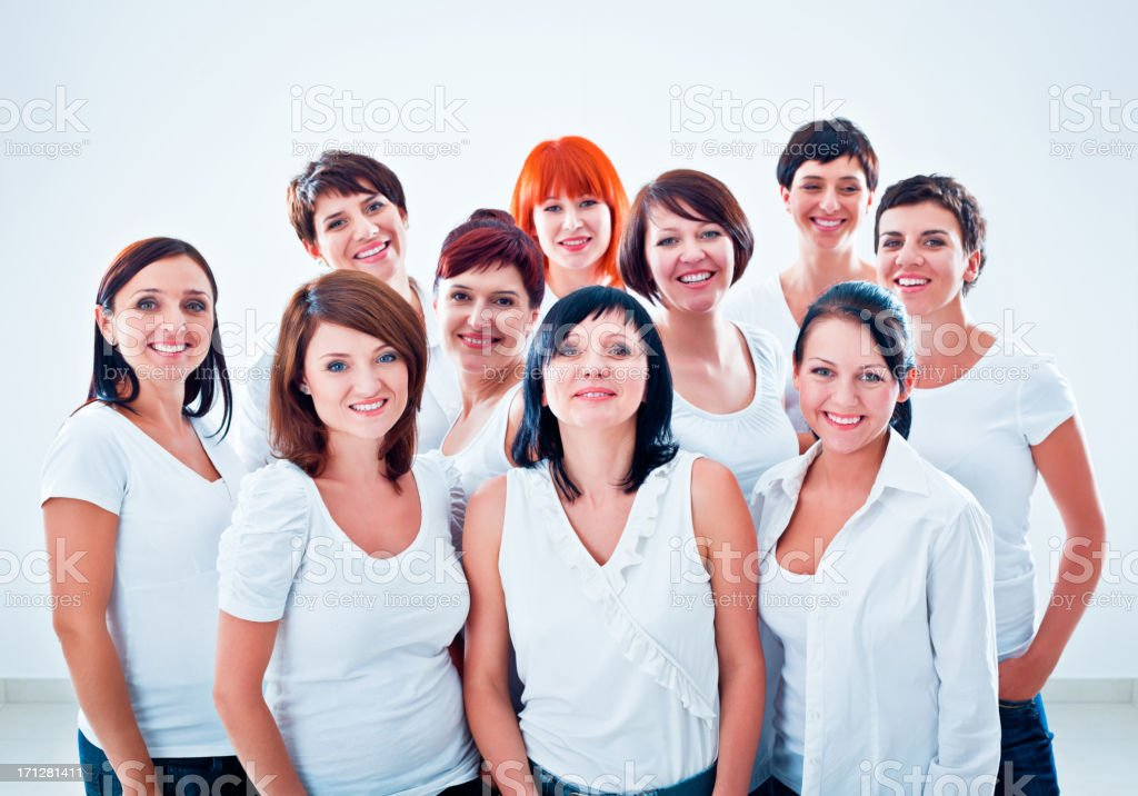 """Women's team """"Large group of happy women standing together against white background, smiling at the camera."""" Adult Stock Photo"""
