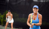 mature woman preparing to play doubles in the volley position.