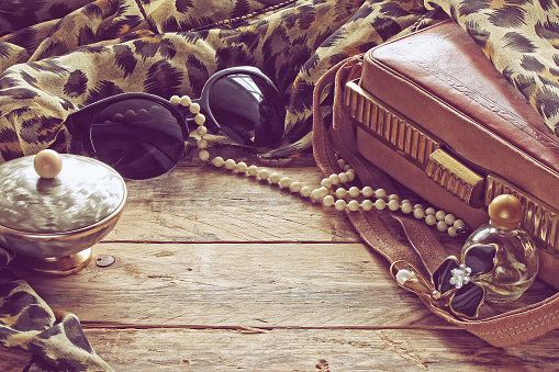womens vintage accessories, powder box, scarf, necklace, sunglasses and handbag on wooden table