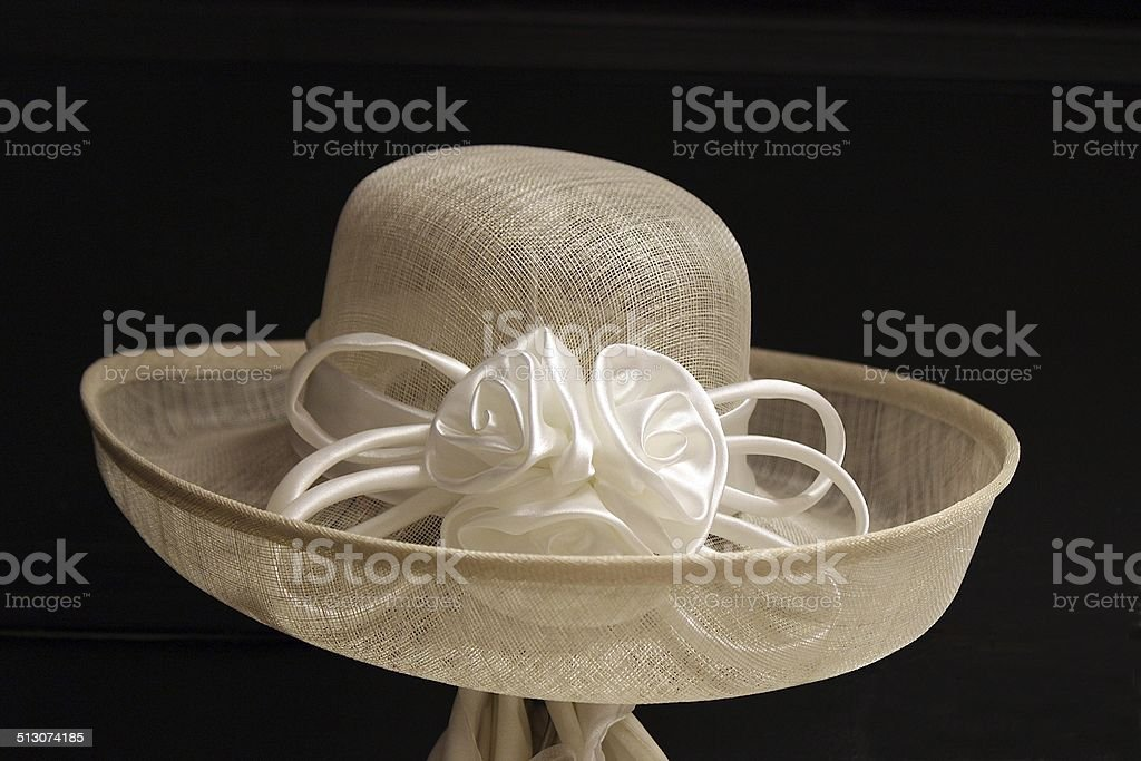 Women's Wide Brimmed Beige Mesh Hat with White Roses stock photo