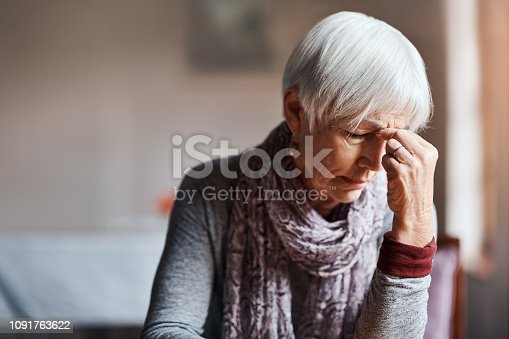 Shot of a senior woman experiencing a headache in a retirement home