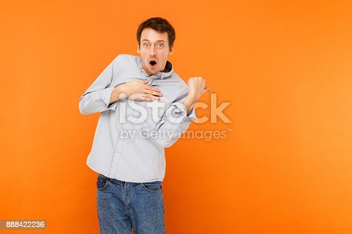 istock Wondered man pointing finger at copy space, open mouth and looking at camera. Have a surprised look . 888422236