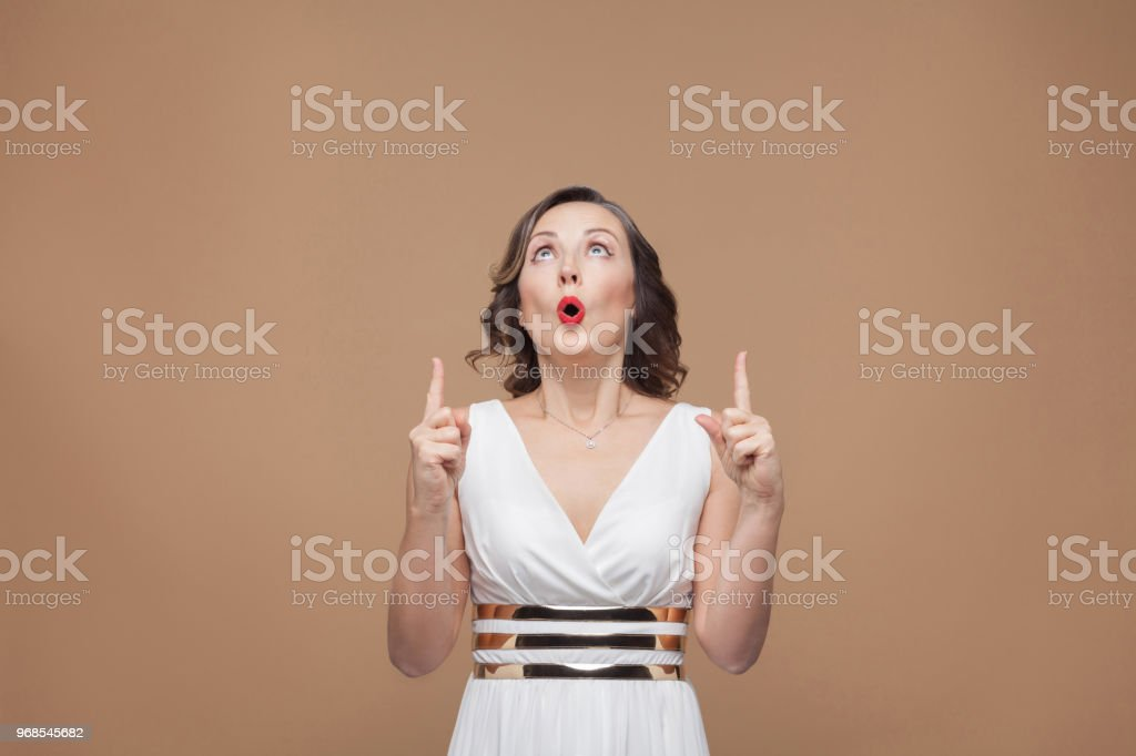 Wondered woman pointing finger up at copy space. Emotion and feeling...