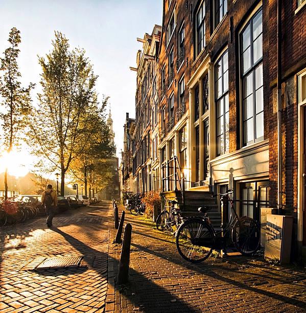 wonderful and idyllic street scene at sunset in amsterdam - walking home sunset street bildbanksfoton och bilder