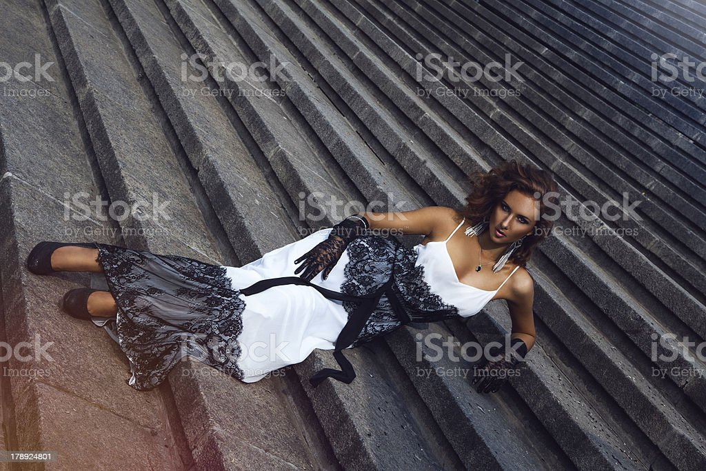 Wonderful brown hair woman lying on stairs royalty-free stock photo