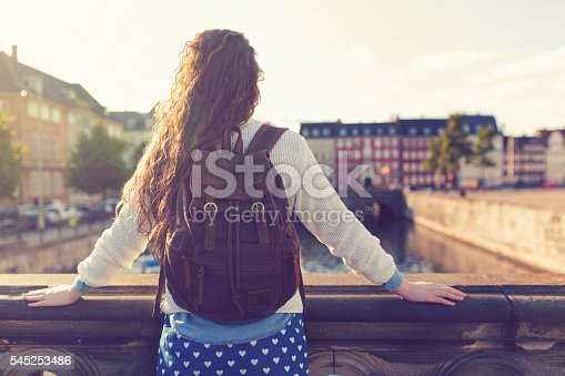 Unrecognizable female person with a backpack on her shoulders standing on the bridge and looking at the cityscape of Copenhagen.