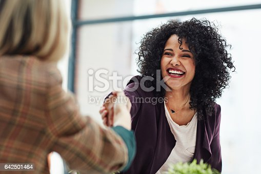 Shot of two colleagues shaking hands during a meeting at work