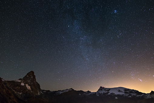 Wonderful starry sky over Matterhorn (Cervino) mountain peak and Monte Rosa glaciers, famous ski resort in Aosta Valley, Italy. Andromeda galaxy clearly visibile mid frame.