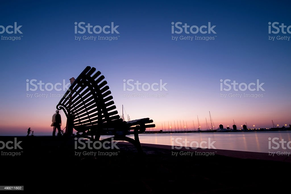 Wonderful sunrise and silhouette on a bench stock photo