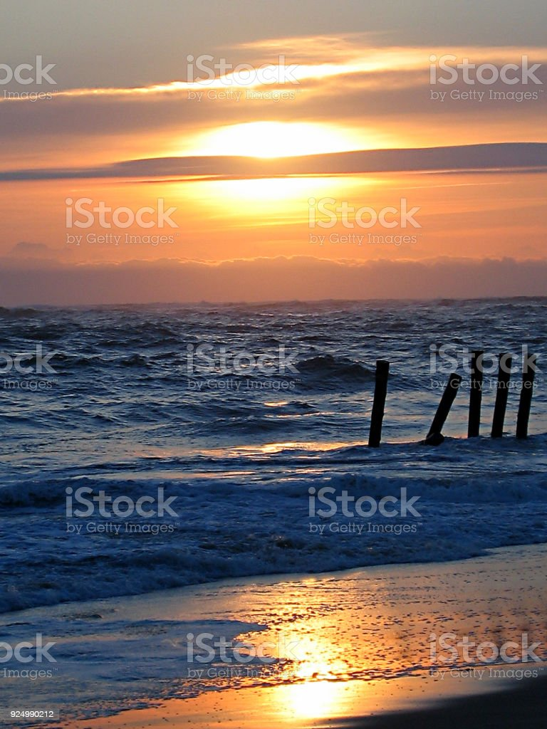 wonderful sunset on wooden wave-breaks on the coast of the atlantic ocean at lege cap ferret in Aquitaine in France stock photo