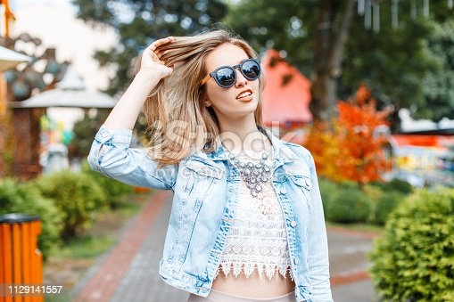 578791454istockphoto Wonderful young hipster woman in a stylish blue denim jacket in black sunglasses in a vintage lace blouse with a necklace in an amusement park on a sunny spring day. Charming stylish girl travels. 1129141557