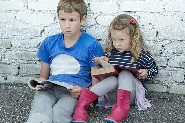 e0fc24fa18edb Wondering sibling children sitting on asphalt ground with books stock photo