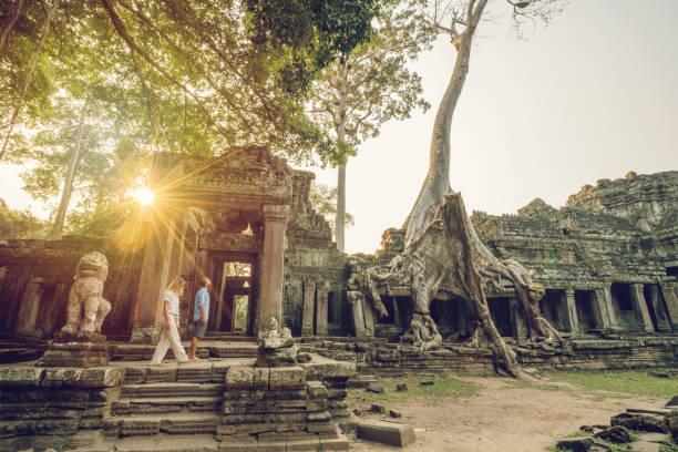 Wonderlust - paar Wandern in antiken Tempel mit Wurzeln, die Übernahme von alten Ruinen - Kambodscha Angkor Wat Komplex bei Sonnenuntergang – Foto