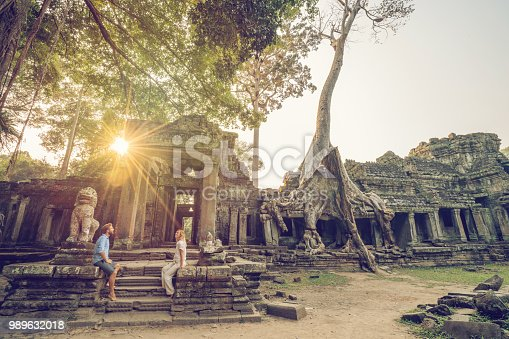 Young couple traveling in Cambodia visiting the temples of Angkor wat complex. People travel discovery Asia concept. Adventure and exploration concept in Siem Reap, Southeast Asia.