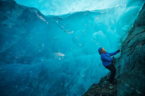 wonderlust in a blue ice cave - アイスクライミング ストックフォトと画像
