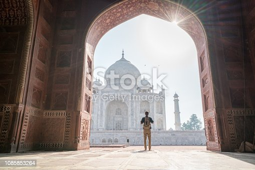 Young man contemplating the famous Taj Mahal at sunrise walking and wandering inside the marvellous monument , Agra, India. People travel Asia concept