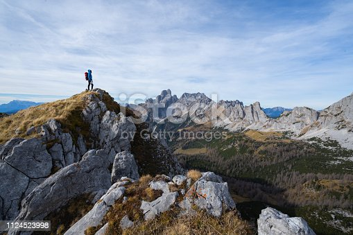 female mountaineer extreme hiker woman with backpack and warm outdoor outfit standing alone high above in mountains on cold windy autumn amazing environment