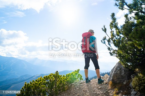 rear view woman with backpack standing on hiking trail in the mountains on sunny autumn day back light