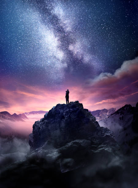 Wonders Of The Night Sky Night sky long exposure landscape. A man standing on a high rock watching the stars rise into the night sky. Photo composite. awe stock pictures, royalty-free photos & images