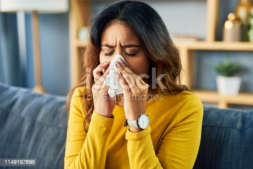 Shot of a young woman blowing her nose while sitting at home