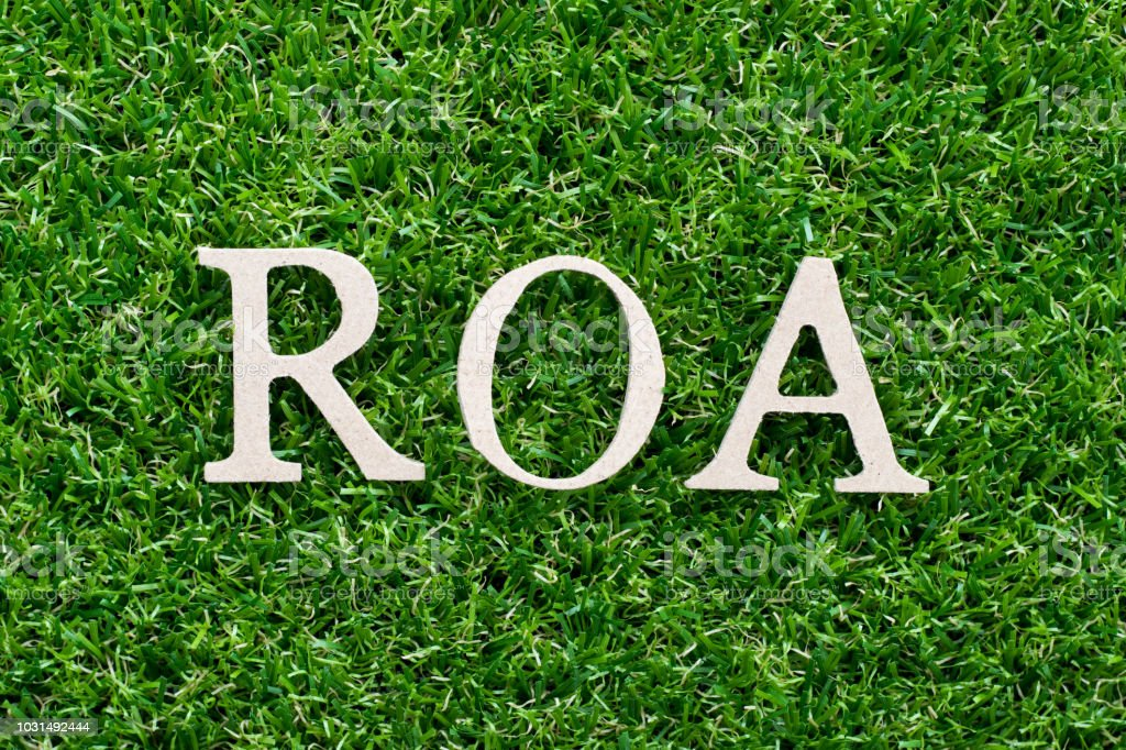 Wood alphabet in word ROA (Abbbreviation of Return on assets) on artificial green grass background stock photo