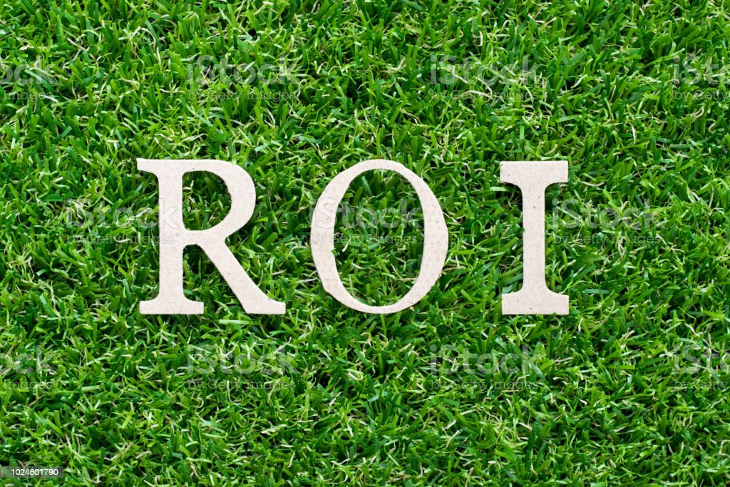 Wood alphabet in word ROI (Abbbreviation of Return on Investment) on artificial green grass background stock photo