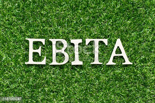 istock Wood alphabet letter in word EBITA (abbreviation of  earnings before interest, taxes and amortization) on artificial green grass background 1137045787