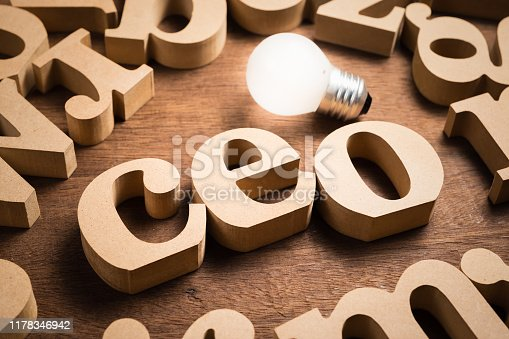 CEO (Chief Executive Officer) wood letters in scattered alphabets with glowing light bulb