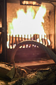 Old basket with wooden logs and fireplace with warm fire at the background.