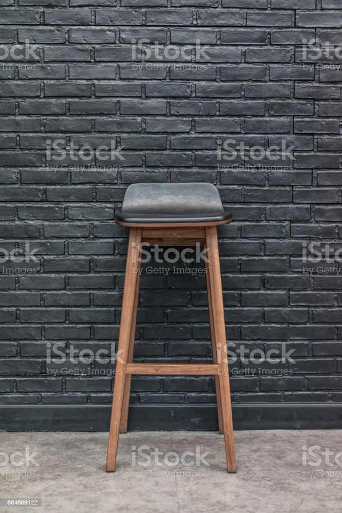 Wood and leather bar chair on black brick wall background, interior concept front view stock photo