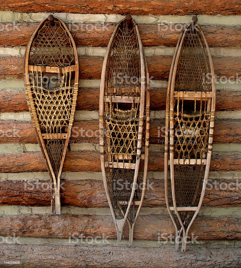 Wood and string snowshoes hanging on pegs stock photo