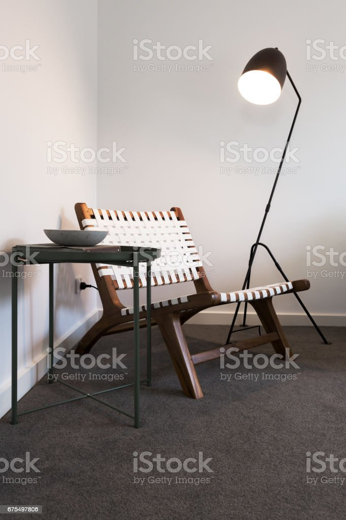 Wood and woven occasional chair with floor lamp stock photo