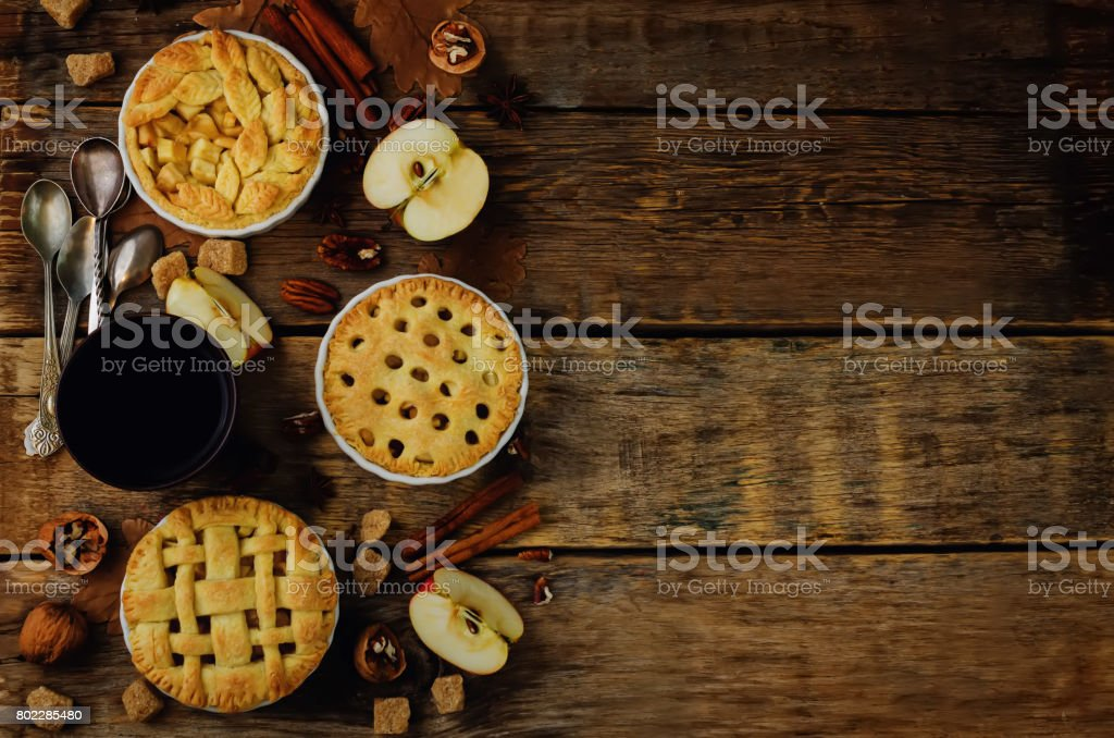 Wood background with apple pies, tea and nuts stock photo