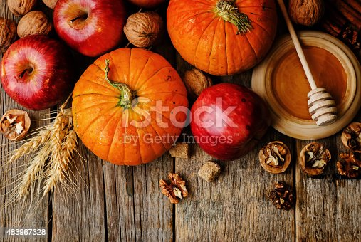 istock wood background with pumpkin, apples, wheat, honey and nuts 483967328