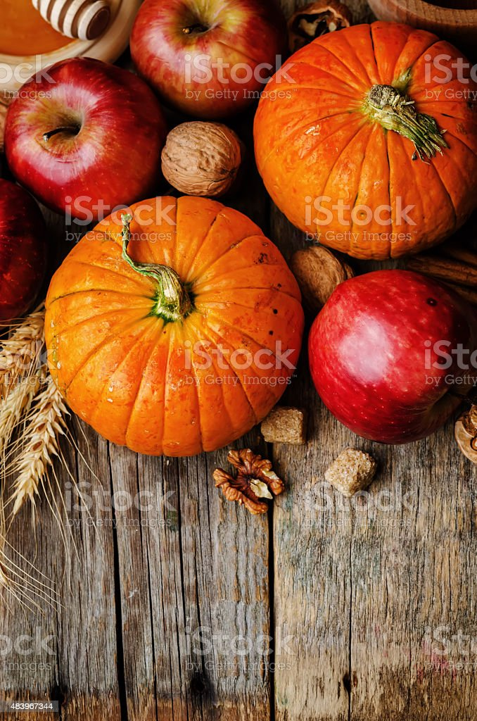 wood background with pumpkin, apples, wheat, honey and nuts stock photo