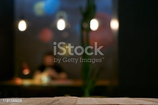 864907996istockphoto Wood Bar Table with Blur Lighting in Night Street Cafe 1131230023
