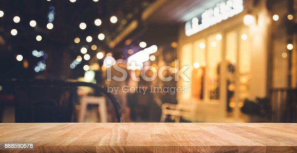864907996istockphoto Wood bar table with blur lighting in night street cafe 888590578