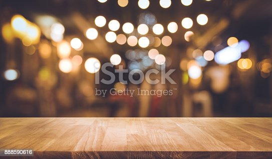 istock Wood bar table with blur lighting in night street cafe 888590616