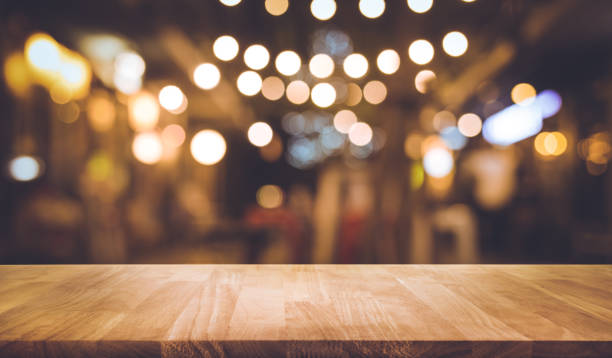 Wood bar table with blur lighting in night street cafe stock photo