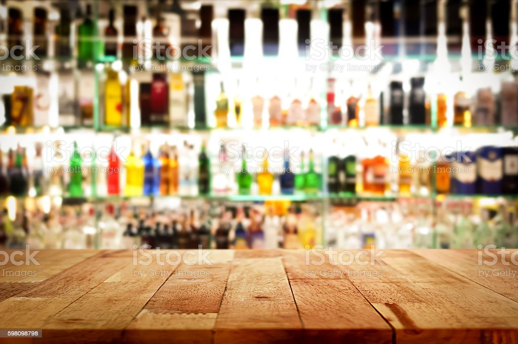 Wood bar top on blur colorful alcohol drink bottle background stock photo