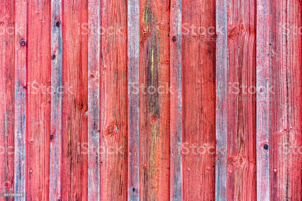 Wood barn wall with red peeling flaking color. Red wooden background texture. stock photo