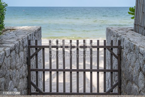 wood barricade and barrier on the stone walkway to the beach.