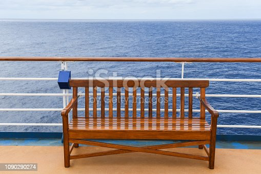 Wooden bench on a cruise ship with the ocean in the background.