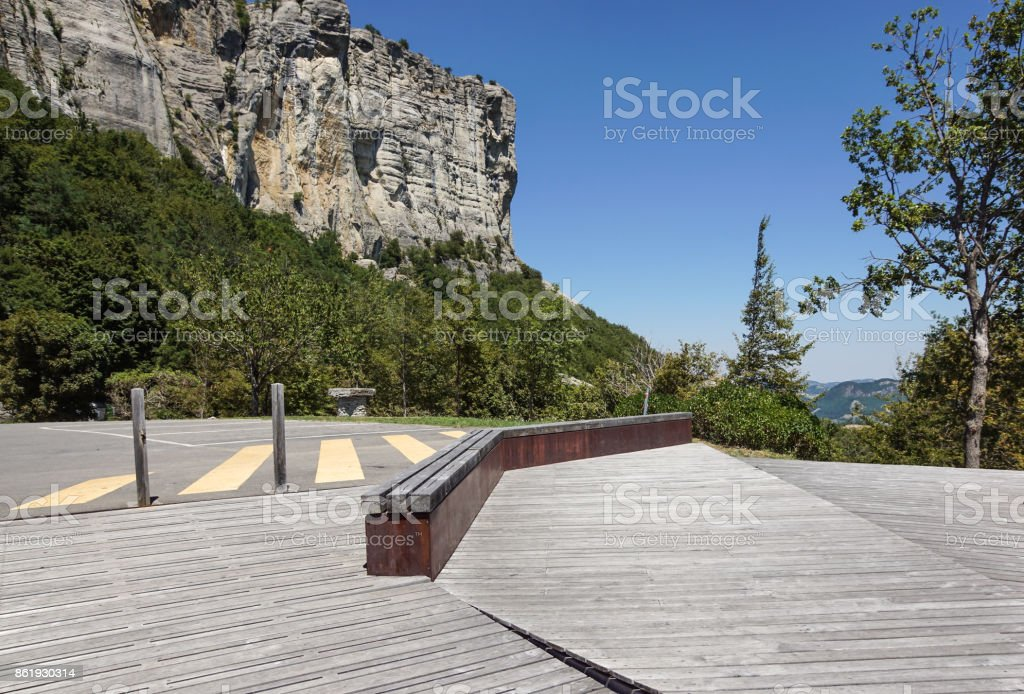 wood bench on the parking area at mountain in italy stock photo