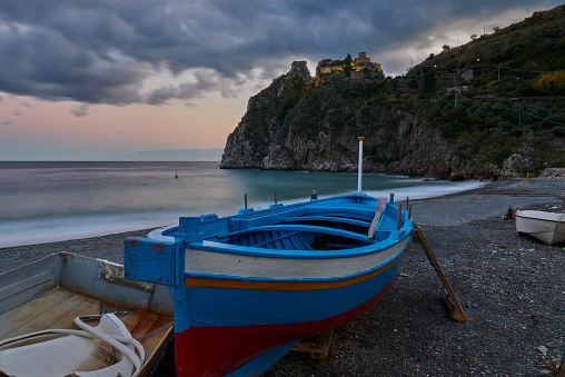 sunset hours on the beach of Taormina, under the castle of Sant'Alessio Siculo with the clouds turning pink and a typical wooden fishing boat in the foreground