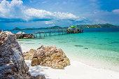 Wood bridge on the beach with water and blue sky. Koh kham pattaya thailand.